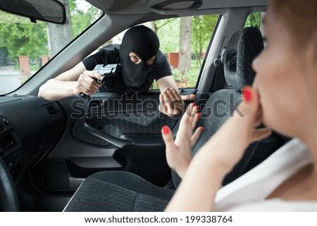 Burglar threatens the woman a gun in the car - stock photo
