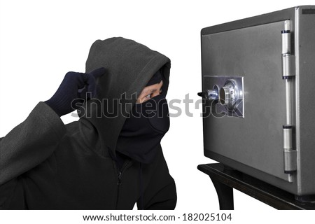 Burglar tries to find the combination lock of a safe deposit box isolated over white - stock photo