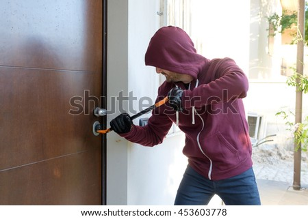 Burglar trying to force a door lock using a crowbar - stock photo