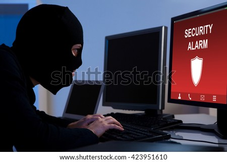 Burglar Wearing A Balaclava Breaking Security Alarm On Computer In Office - stock photo