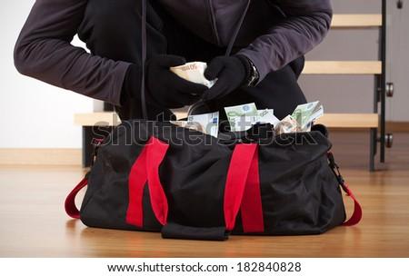 Burglar wearing gloves counting the stolen money - stock photo