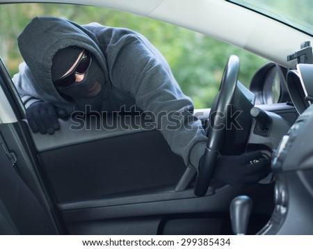 Burglar wearing mask balaclava stealing car key - stock photo