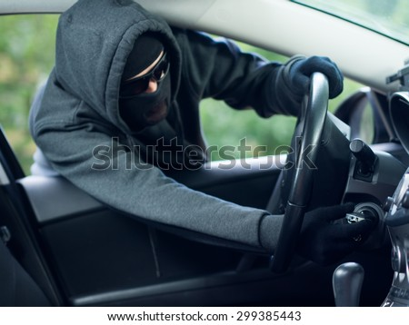 Burglar wearing mask balaclava stealing car key