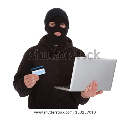 Burglar Wearing Mask Holding Credit Card And Laptop Over White Background