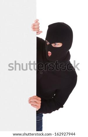 Burglar With Balaclava Holding Blank Placard Isolated On White Background - stock photo