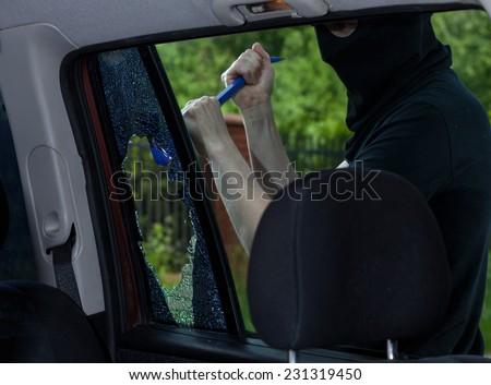 Burglar with crowbar breaking car window, horizontal - stock photo