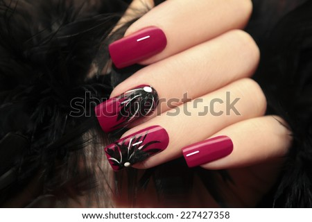 Burgundy manicure with design on the nails and feathers. - stock photo