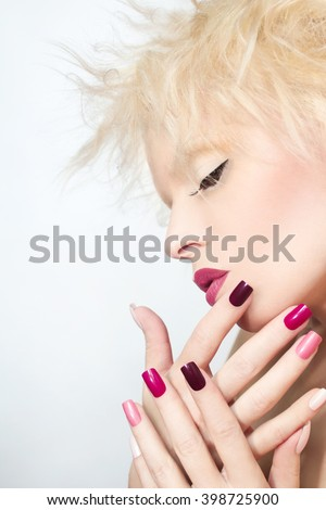 Burgundy multi-colored manicure and makeup on the blonde girl with the flower on his head. - stock photo