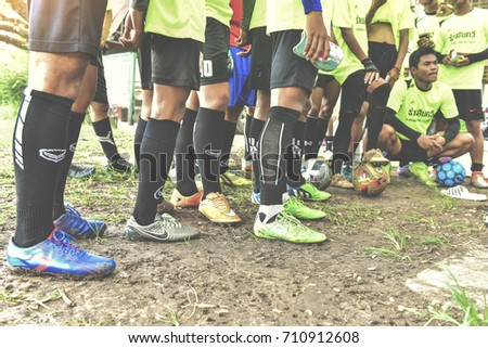 BURIRAM,THAILAND - JUNE 25,2017: Close-up of legs wearing Stud shoes.UnIdentified of Youth Football Players standing and listening to coaching, JUNE.25.2017
