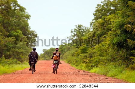 BURKINA FASO - AUGUST 11: Male and female African cycling, the bicycle is the popular means of transport, August 11, 2009 in Tiebele, Burkina Faso