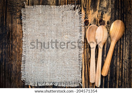Burlap and rural kitchen utensils on vintage wooden table  view from top. Rustic background with free text space - stock photo