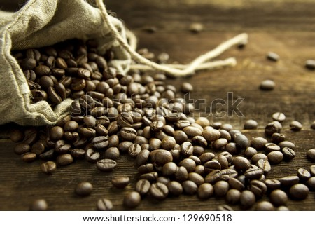 Burlap bag filled with coffee beans on dark wooden board, selective focus - stock photo