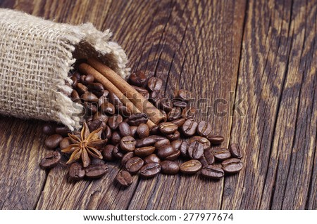 Burlap bag with coffee beans on dark wooden board - stock photo