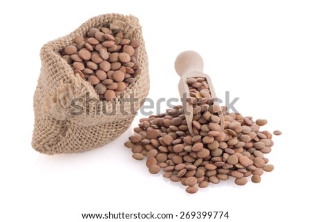 Burlap bag with lentils and wooden scoop on white background. - stock photo