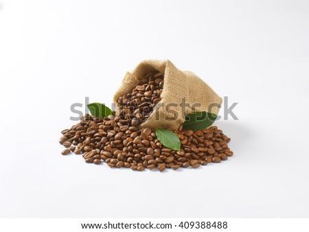 burlap sack full of coffee beans on white background - stock photo