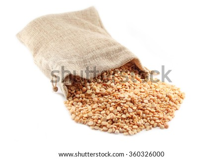 Burlap sack with dried peas spilling out over a white background.