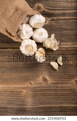 Burlap sack with garlic on a wooden background