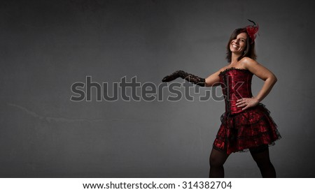 burlesque dancer showing with open arm, dark background - stock photo