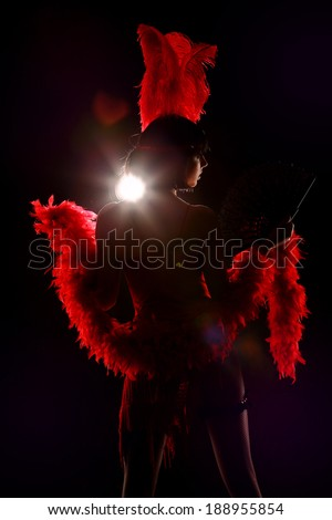 Burlesque dancer with red plumage and red short dress, black and red background, on the stage - stock photo