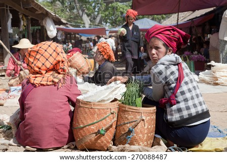 BURMA, SHAN STATE, SAMKAR -  FEBRUARY 25, 2011: Pa-O tribal woman in native costume are sitting on the market are selling home-made food.