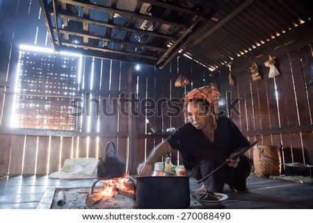 BURMA, SHAN STATE, SAMKAR -  FEBRUARY 25, 2011: Pa-O tribal woman in native costume is cooking on open fire place in her shanty kitchen. - stock photo
