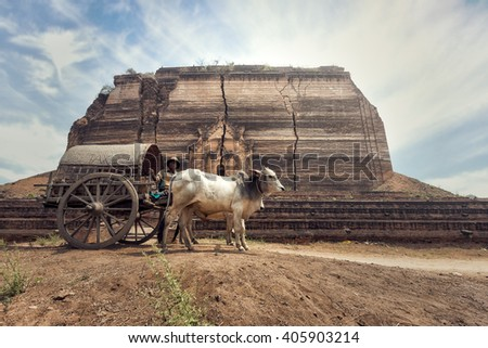 Burmese rural man driving wooden cart with traditional village life in Burma countryside - stock photo