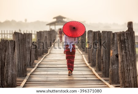 Burmese woman holding traditional red umbrella and walking on U Bein Bridge - stock photo