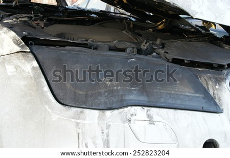 Burn sports car wreck - right front light - stock photo