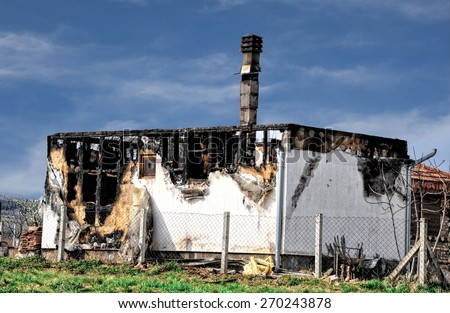 burned-out house after a fire on a background of blue sky - stock photo
