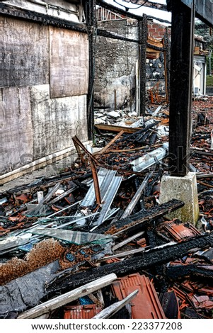 Burned wreck ruins of destroyed commercial building with scattered burn debris of twisted metal and broken glass after intense burning fire disaster waiting for investigation of arson for insurance  - stock photo
