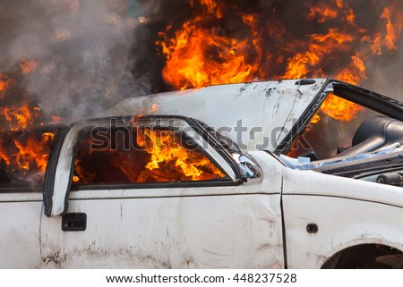 burning and then extinguish an old white car - Exercise firefighters - stock photo