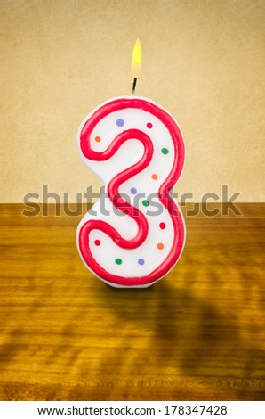 Burning birthday candle number 3 - stock photo