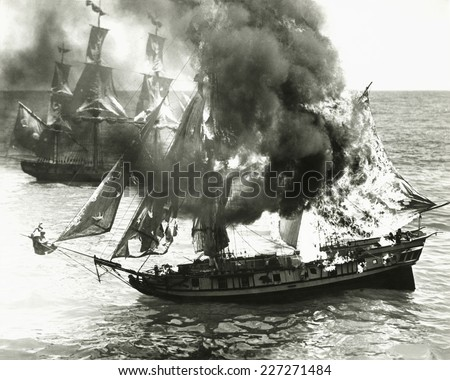 Burning boat in the middle of the ocean - stock photo
