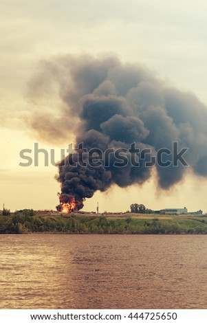 Burning building with flames and black smoke near the water - stock photo