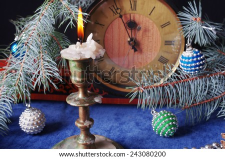 Burning candle and clock with christmas decoration