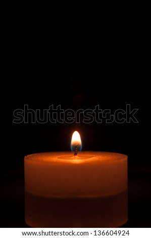 Burning candle and its subtle reflection on a black background