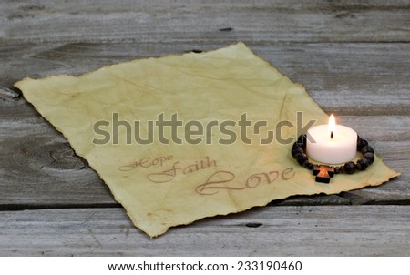 Burning candle and wooden cross on antique parchment paper with Hope, Faith, Love with rustic wooden background - stock photo