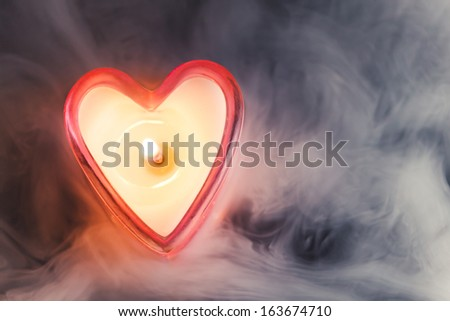 burning candle heart in dense fog