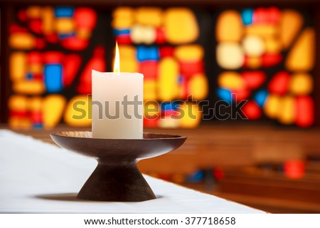 burning candle in a church with the stained-glass window at the background. Location: New Zealand, North Island, Wellington - stock photo