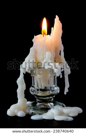 Burning candle in glass candlestick on a black background - stock photo