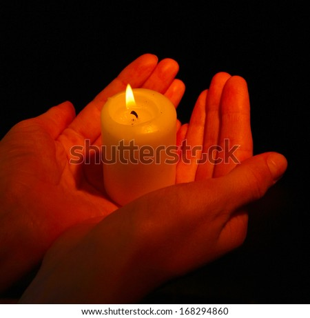 Burning candle in hands isolated on black - stock photo