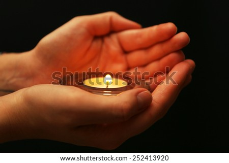 Burning candle in hands on dark background - stock photo