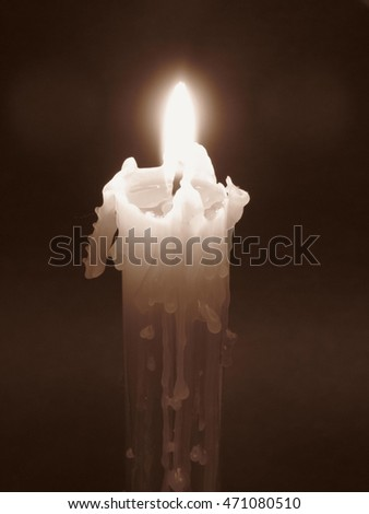 burning candle in the darkness in ochre tones