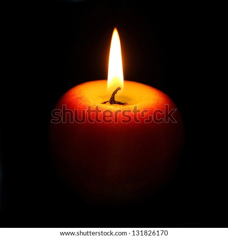 burning candle in the shape of an apple on a black background