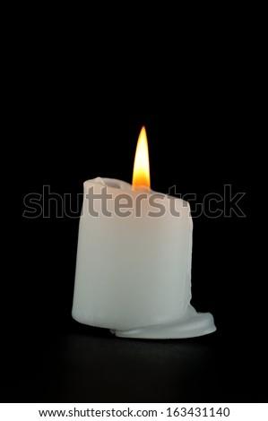 Burning candle isolated on black background - stock photo