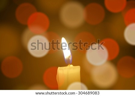 Burning candle light on abstract color bacground. Colorful bokeh