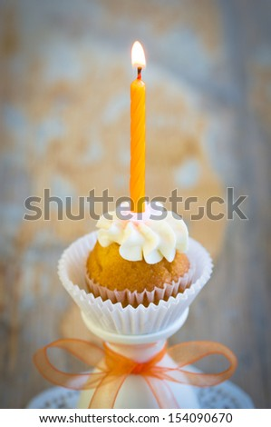 Burning candle on tiny birthday cupcake. Selective focus on fire - stock photo