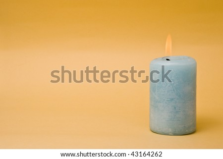 Burning candle over a yellow background - stock photo