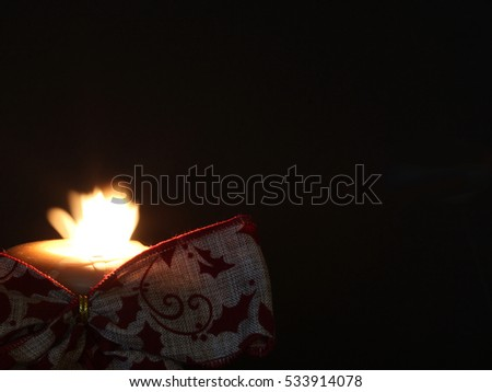 Burning Candle with Burlap Ribbon - Photograph of a burning candle with a moving flame and a burlap ribbon in front of the candle.  Dark background for text.