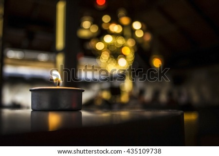 Burning candle, with defocussed fairy lights, bokeh in the background, Festive Christmas background with copy space - stock photo